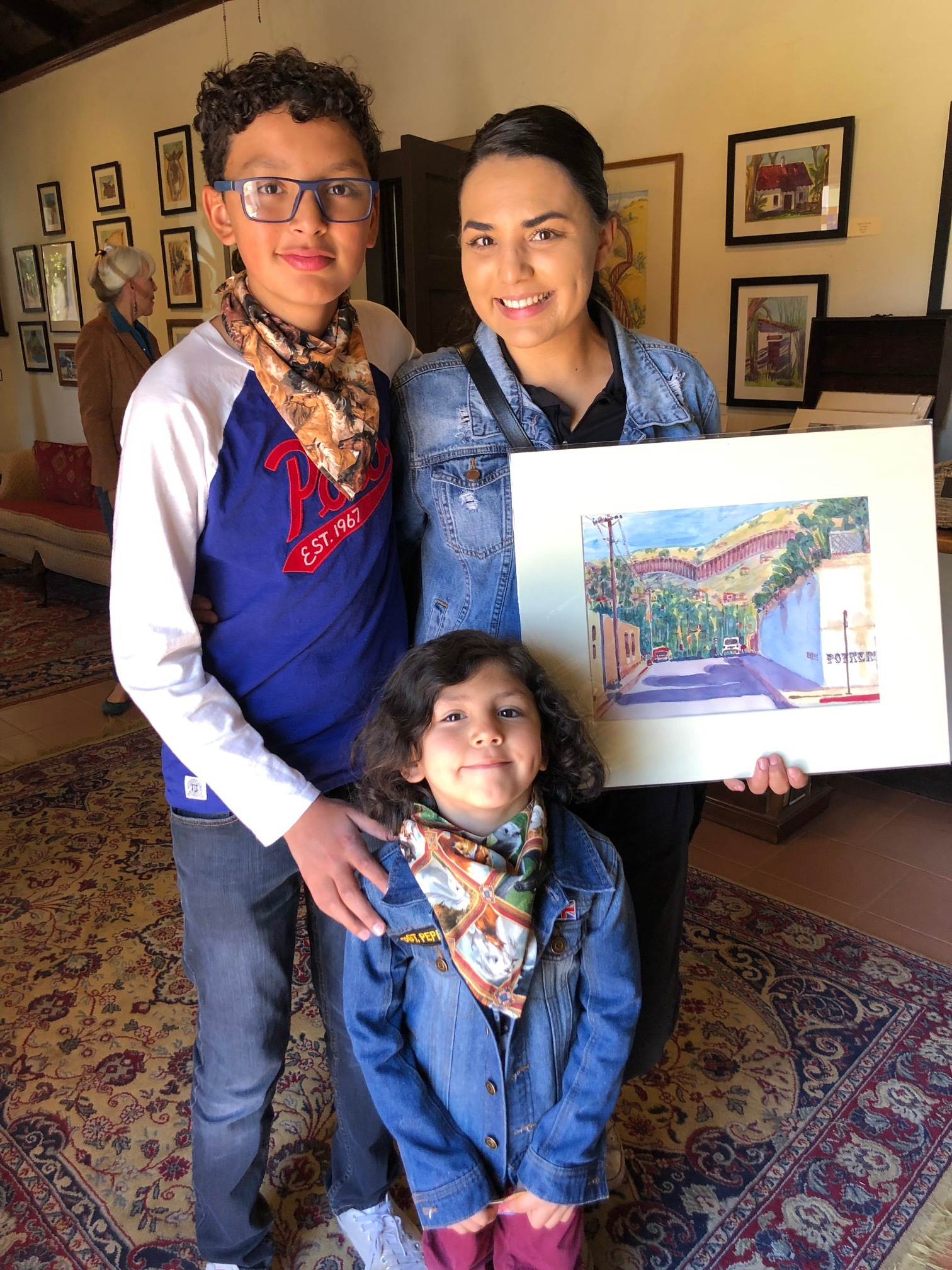 "- Nogales resident Patricia Gomez and her sons at Rancho Santa Cruz Open Studio 2019, proud owners of an original watercolor entitled ""Ellis at Potrero."""
