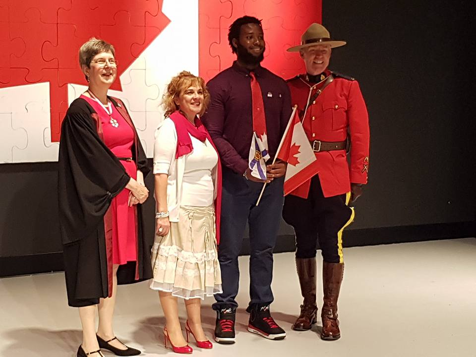 Stephen Robinson-Enebeli (centre right) stands with (from left to right) Dr. Mary Ann White, a recipient of the Order of Canada who presided over the citizenship ceremony; the Honourable Lena Diab, Minister of Immigration and Minister of Acadian Affairs and Francophonie; and a member of the Royal Canadian Mounted Police.