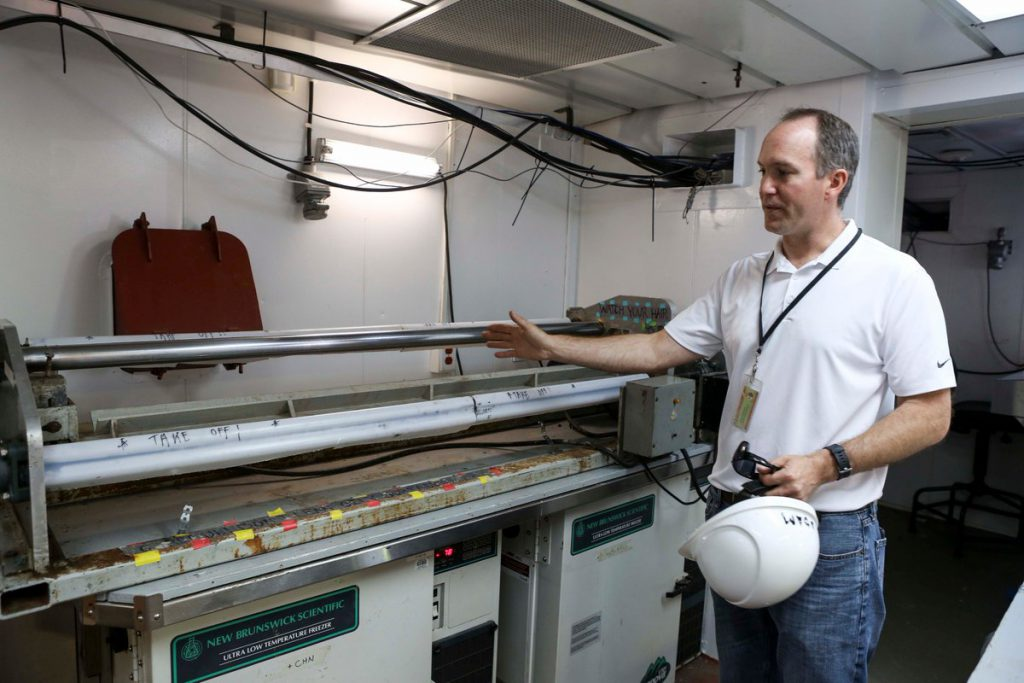Adam MacDonald, NS Department of Energy & Mines, examines a core sample taken during an offshore coring cruise. (Source: Genome Atlantic)
