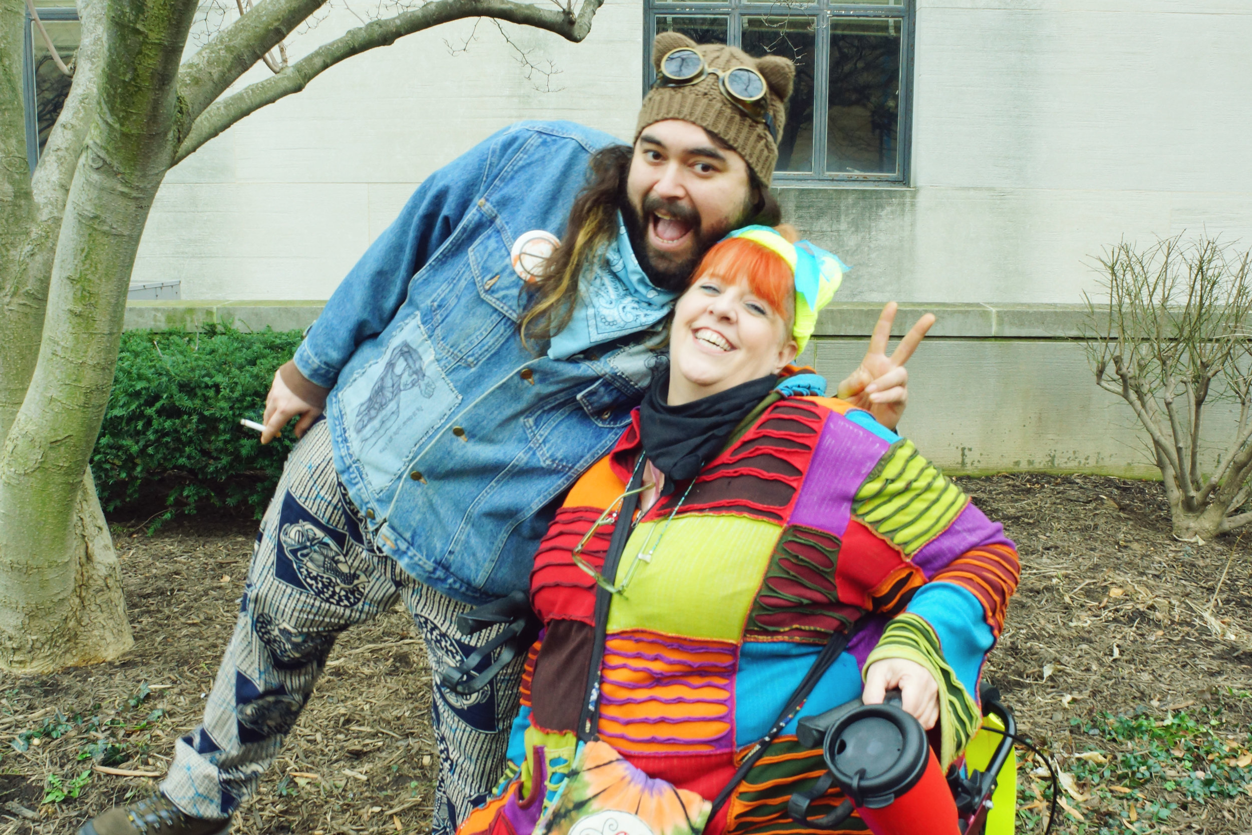 [Image description: A bearded, long-haired Latino man, Rico,smiles and flashes a peace sign over the shoulder of a beaming red-haired woman, Lainie.She wears a brightly colored patchwork coat and holds a red thermos.]