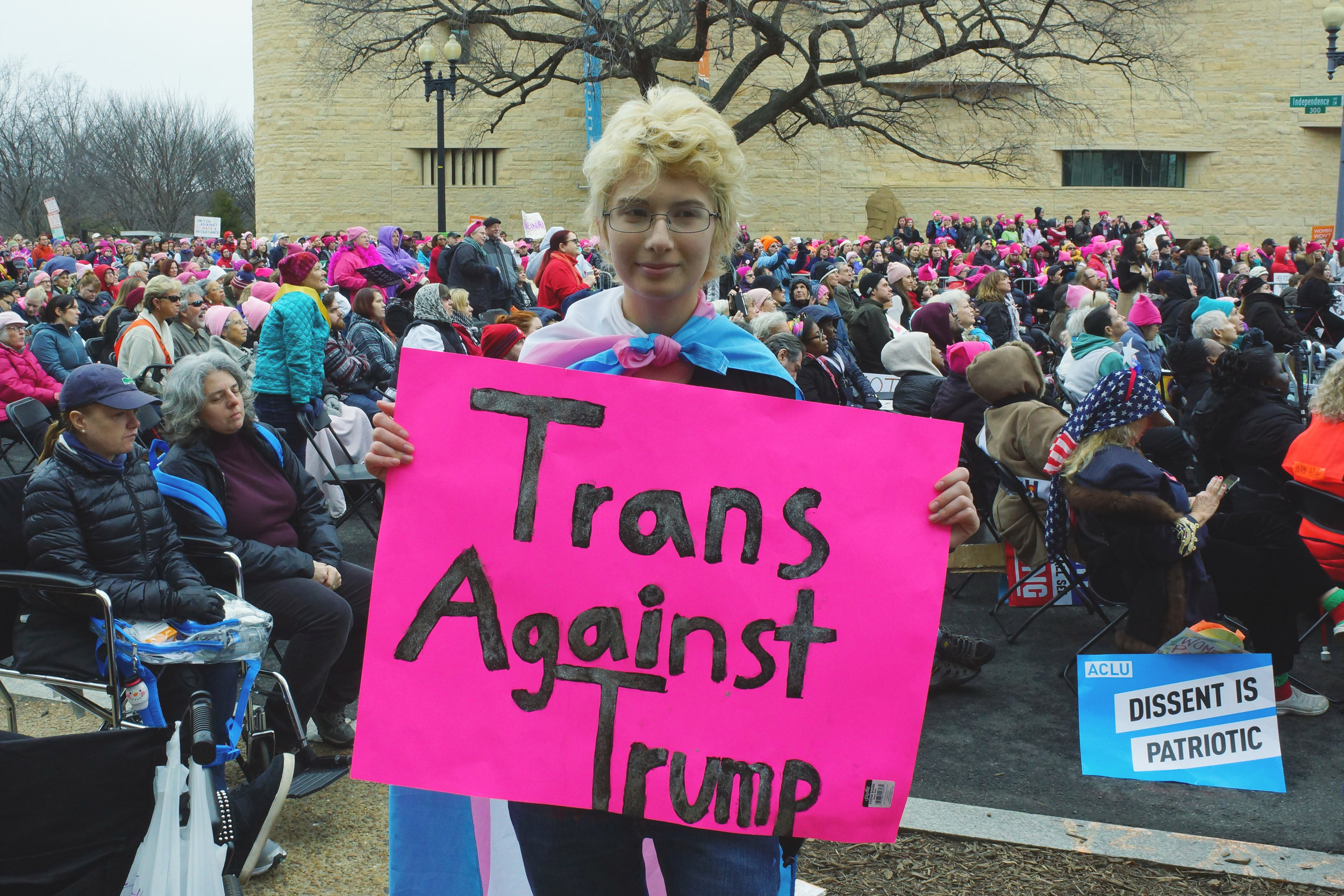 """[Image description: Alex, a blond trans* boy in glasses stands wearing a trans flag as a cape and carrying a pink sign with the words:""""Trans Against Trump."""" In the background, a large crowd is facing a the stage, not pictured. Resting against a chair to the right is an ACLU """"Dissent is Patriotic."""" sign]"""