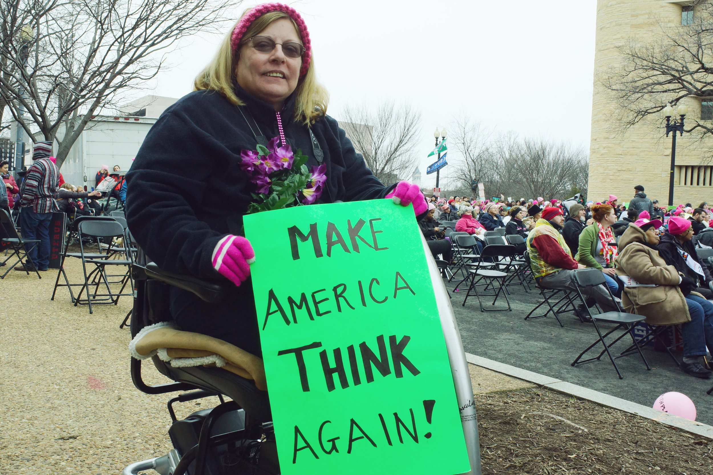 """[Image description: Anne Marie, a white woman with blonde hair and a pink knitted headband sits in a mobility scooter, smiling at the camera. She holds a green sign with black writing that says """"Make America Think Again!"""" and has a bouquet of flowers pinned to her jacket.]"""