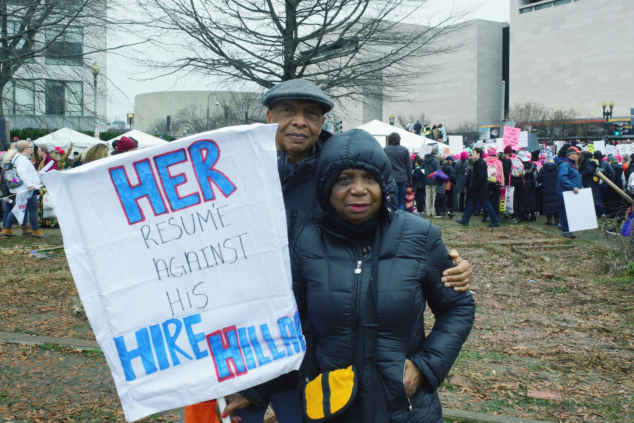 """[Image description: Virgil and Mary, an older black couple in winter coats stand holding a sign that says """"Her resume against his. Hire Hillary."""" Virgil wears a cap and has his arm around the Mary's shoulder. They look into the camera with serious expressions.]"""