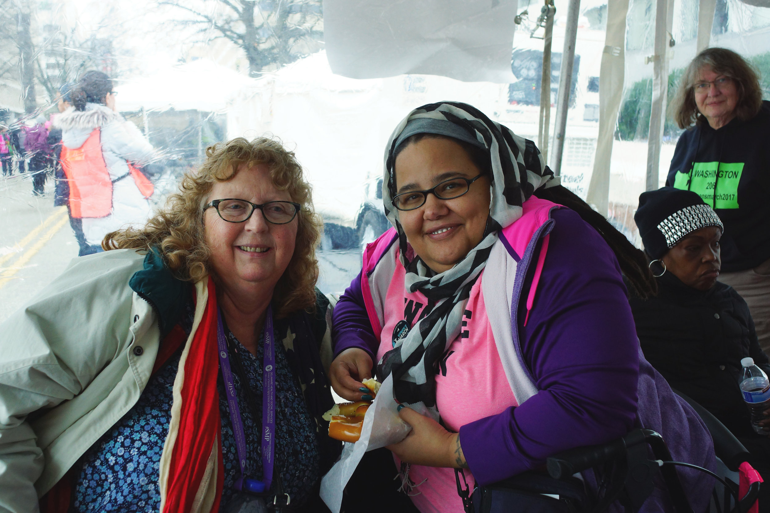 [Image description: Two women in wheelchairs lean toward each other and smile for the camera. The woman on the left, Cathy, is an older white woman with curly hair, glasses, and a red scarf. The women on the right, Kim, has dark skin and wears glasses and a black and white checkered hijab. She holds a hot pretzel and is wearing a bright purple and pink jacket.]