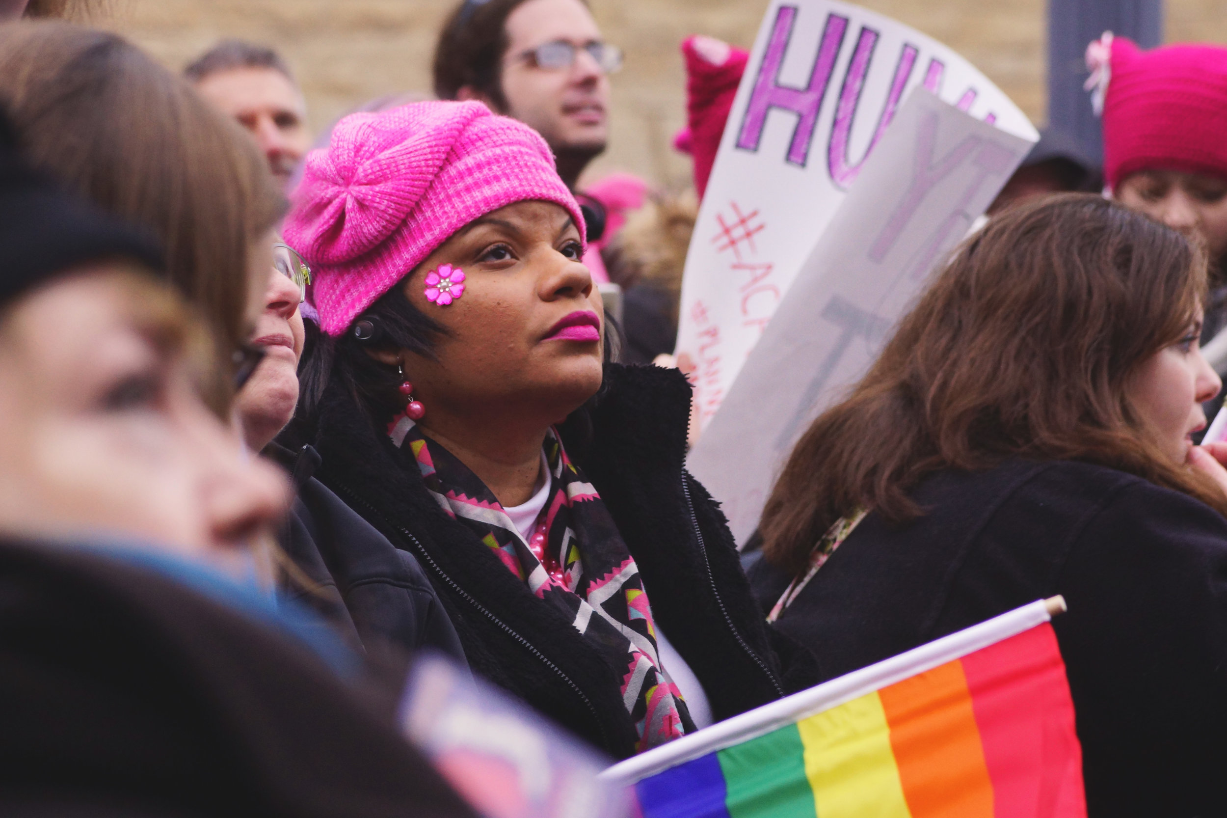 [Image Description: A black woman in a pink hat, with matching lipstick and a bejeweled flower on her cheek sits in the ADA seating area. A rainbow flag is resting at her side.]