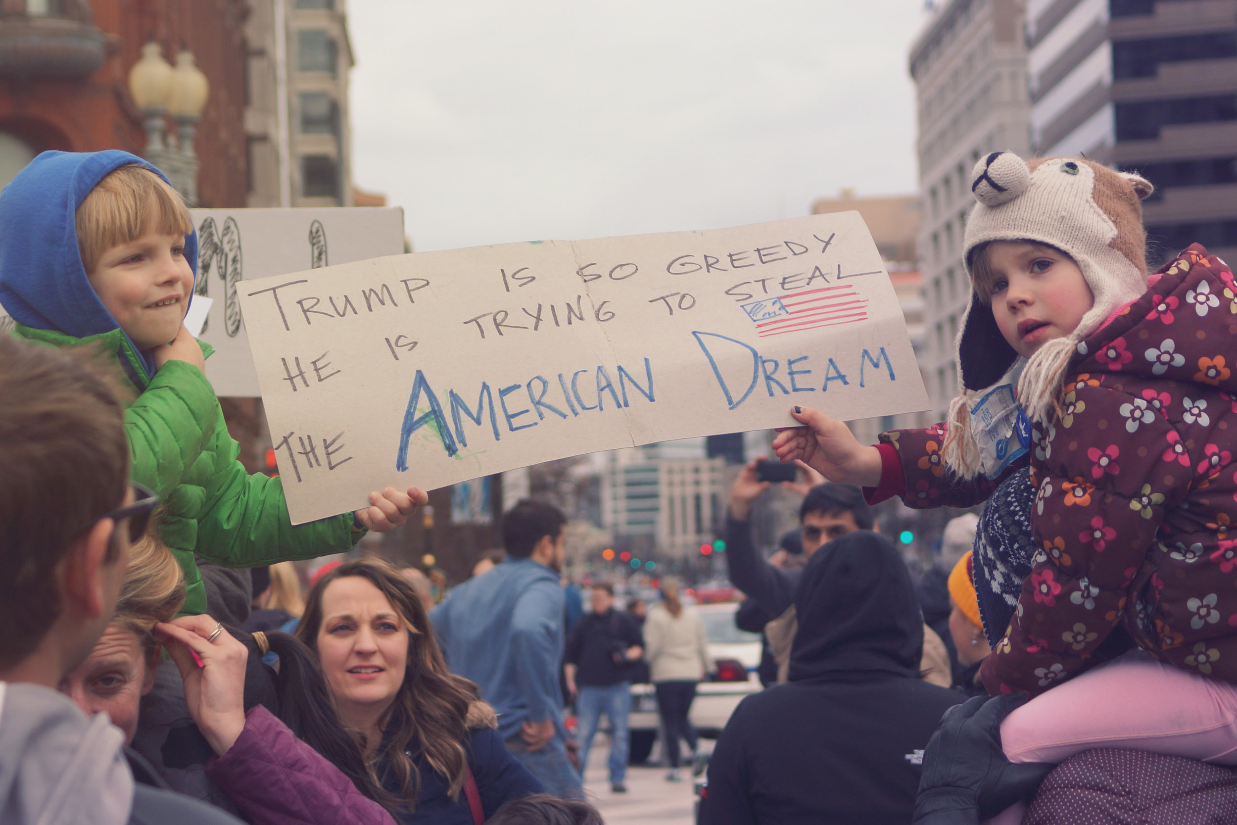 [Image Description: At either end of the photo a white child sits on the shoulders of an adult, one is wearing a bear hat and floral puffer jacket, the other a hoodie and giving a toothy grin.They hold a sign between them in the air that reads 'Trump is so greedy he is trying to steal the American dream.']