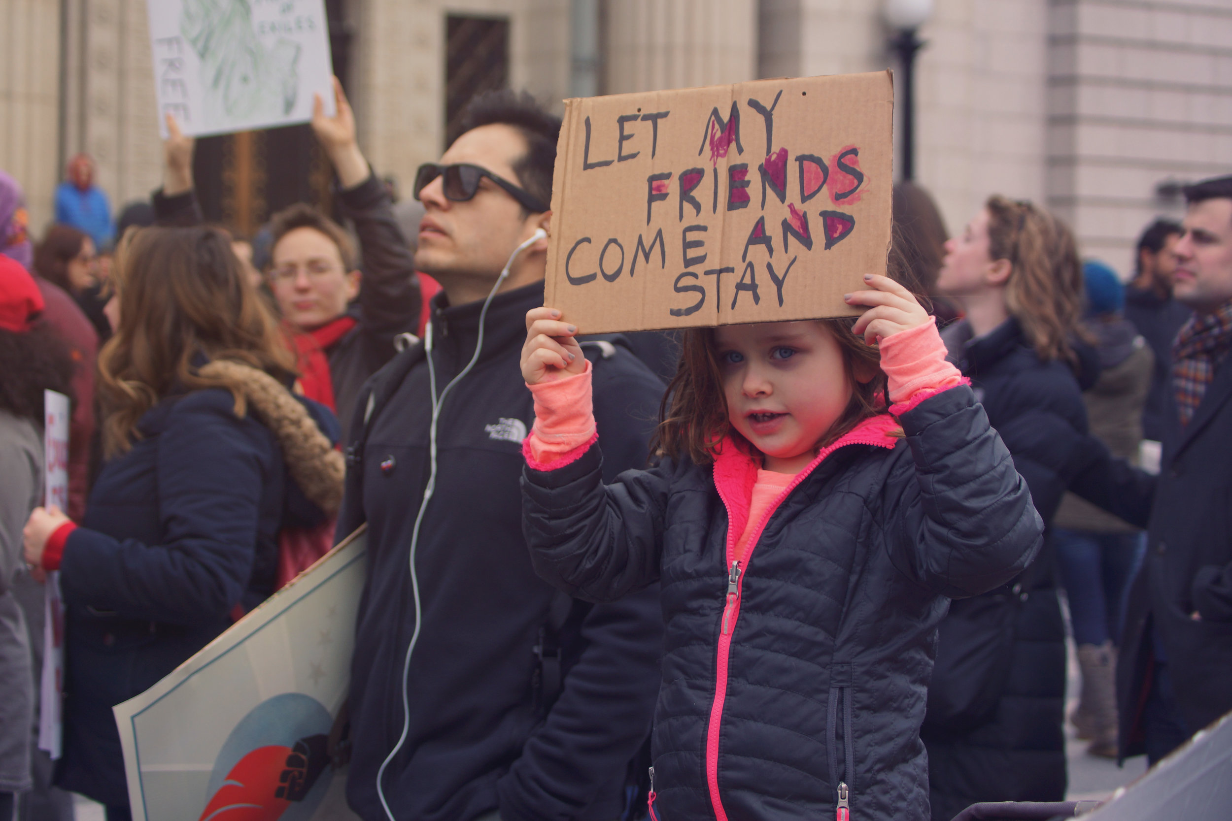 [Image Description: A light skinned girl holds a colourful sign above her head that says 'let my friends come and stay.']