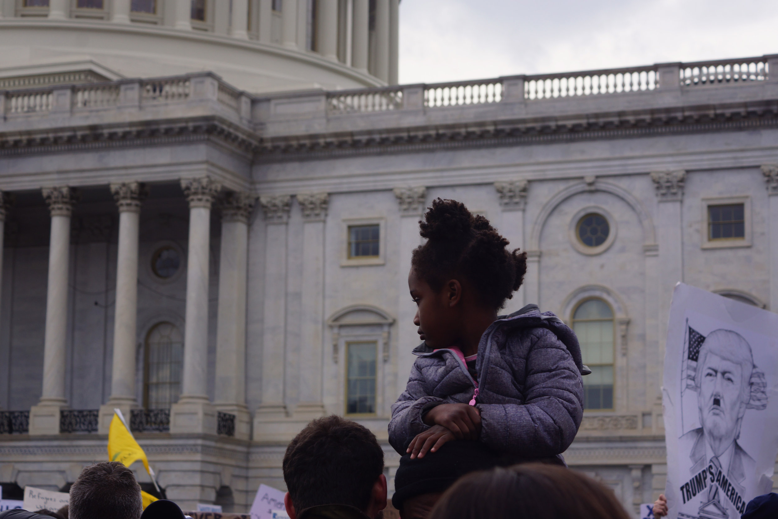[Image Description: A young black girl sits on an adult's shoulders, resting her hands on their head, looking at the Capitol building pensively. A sign behind her has a drawing of Donald Trump with Hitler's moustache, and reads 'Trump's America' beneath the picture.]