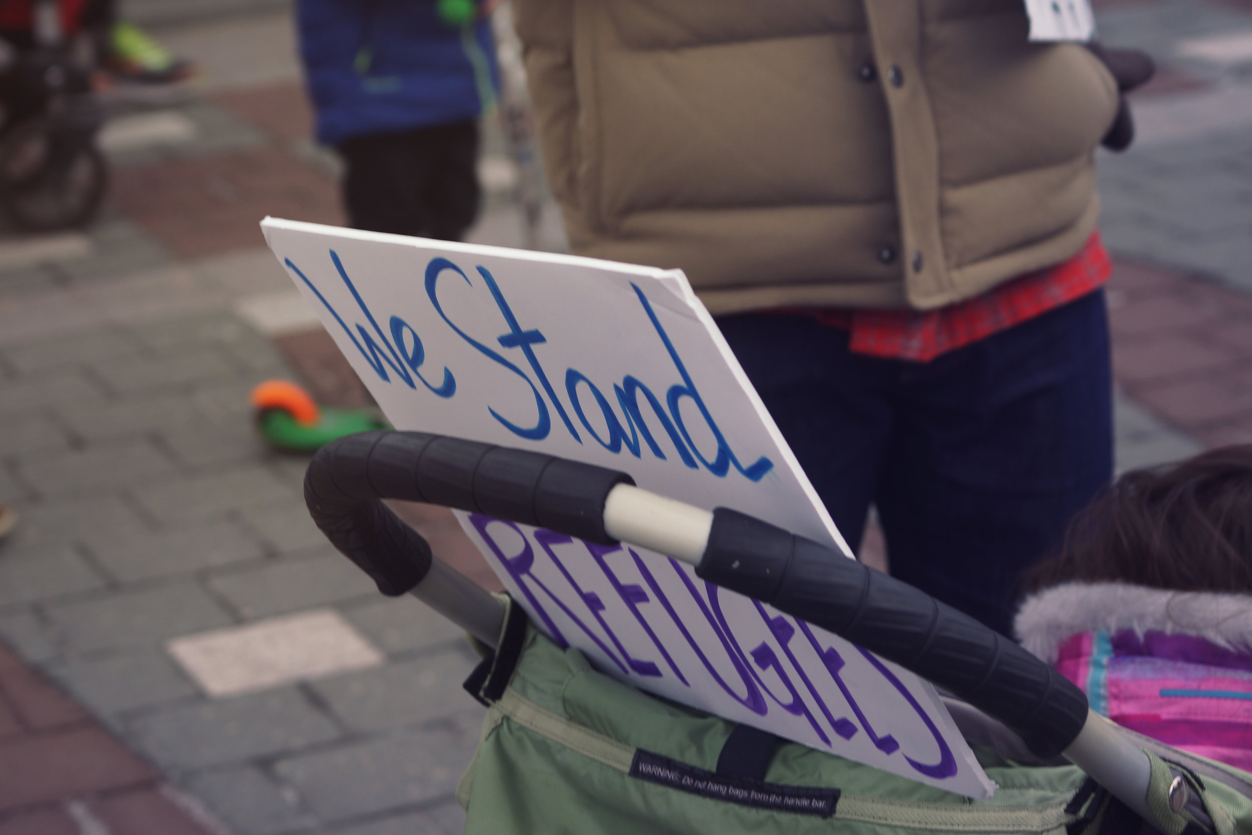 [Image Description: A sign sits at the top of a stroller behind a child's head. Seen clearly is 'We stand...Refugees.']