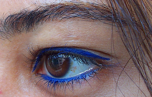 Nisha A / Creative Commons  [Image Description: close-up photograph of a brown eye lined with blue eyeliner. Strands of dark hair are visible at the right side of the photograph.]