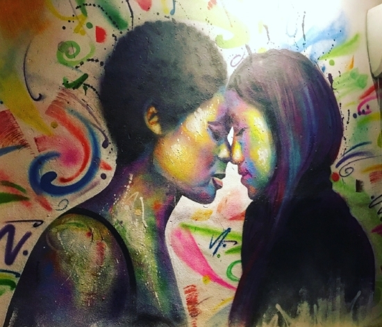 [Image description: photograph of a brightly coloured mural inside L Bar. It depicts two people facing one another in profile, with their noses and foreheads touching and their eyes closed.]  Cristina Maza