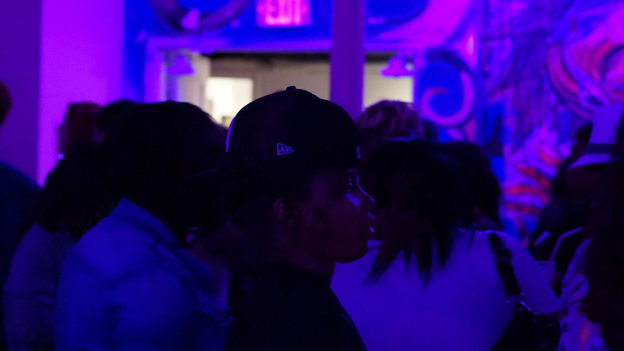Soph Bonde/Argot Magazine. [Photo description: A young Black woman in a baseball cap walks through a crowd at a party in dim lighting].