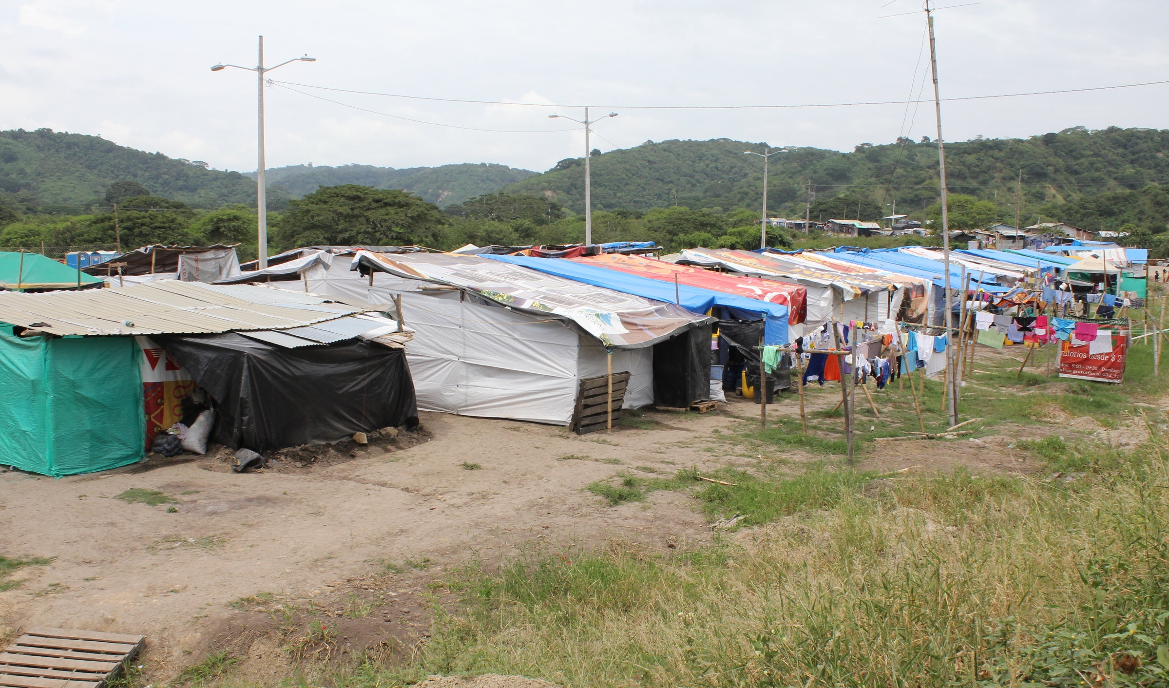 [Image description: photograph of an unofficial refugee camp in Canoa, Manabi Province, Ecuador. Tarpaulins, bedsheets and newspapers stretch between wooden poles to form walls and roofs, and washing lines hang outside the tents to the right of the picture.]  Kimberley Brown