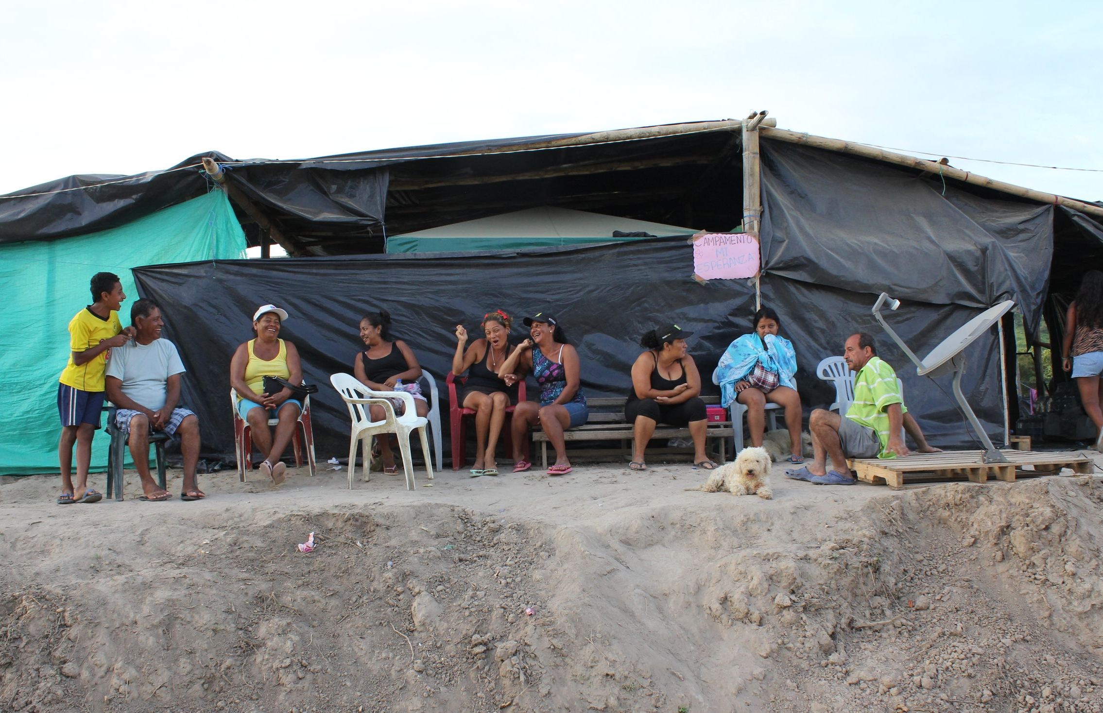 "[Image description: photograph of people laughing and talking outside ""Campamiento Mi Esperanza"", an unofficial refugee camp in Canoa, Manabi Province, Ecuador. They are sitting in plastic chairs, in front of a tent made of tarpaulins and bamboo poles.]  Kimberley Brown"