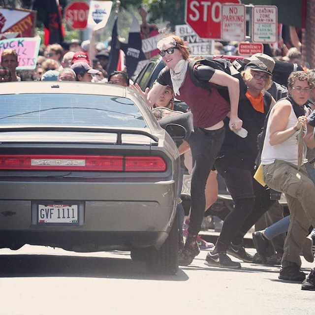 I had more good pictures from Saturday but then I got run over by a Nazi (twice) and lost my phone.   [Photo description: The author is seen wearing a bandana and protective goggles, jumping out of the way as the car that drove into the protestors in Charlottesville and killed Heather Heyer. Anti-fascist and Black Lives Matter signs wave in the background.]