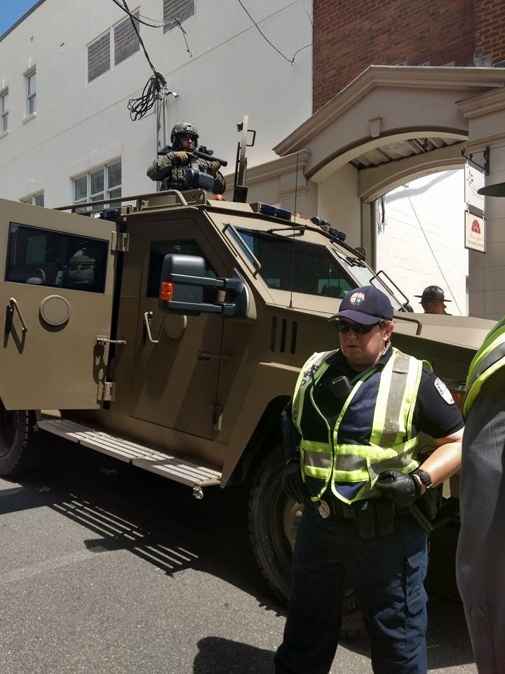 [Photo description: a white male police officer with a hand on the baton in his belt stands in front of a military armored truck. On top of the truck,a white man in full military gear brandishes a grenade launcher.]