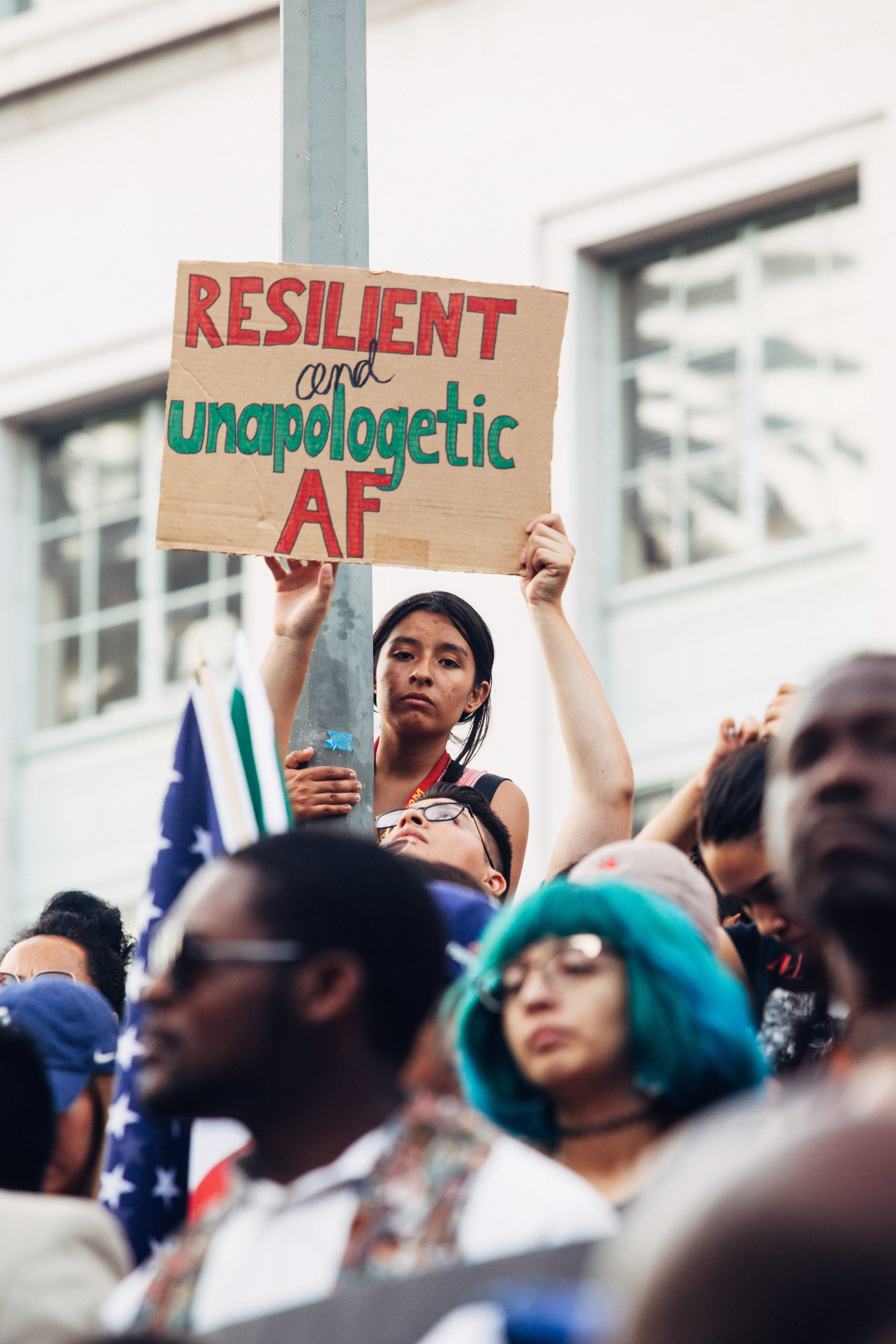 """[ Photo description: a young Latina woman stares down from a perch on a lamppost, onto a diverse crowd of protesters. In front of her, a young man holds a sign saying """"Resilient and unapologetic AF""""]"""
