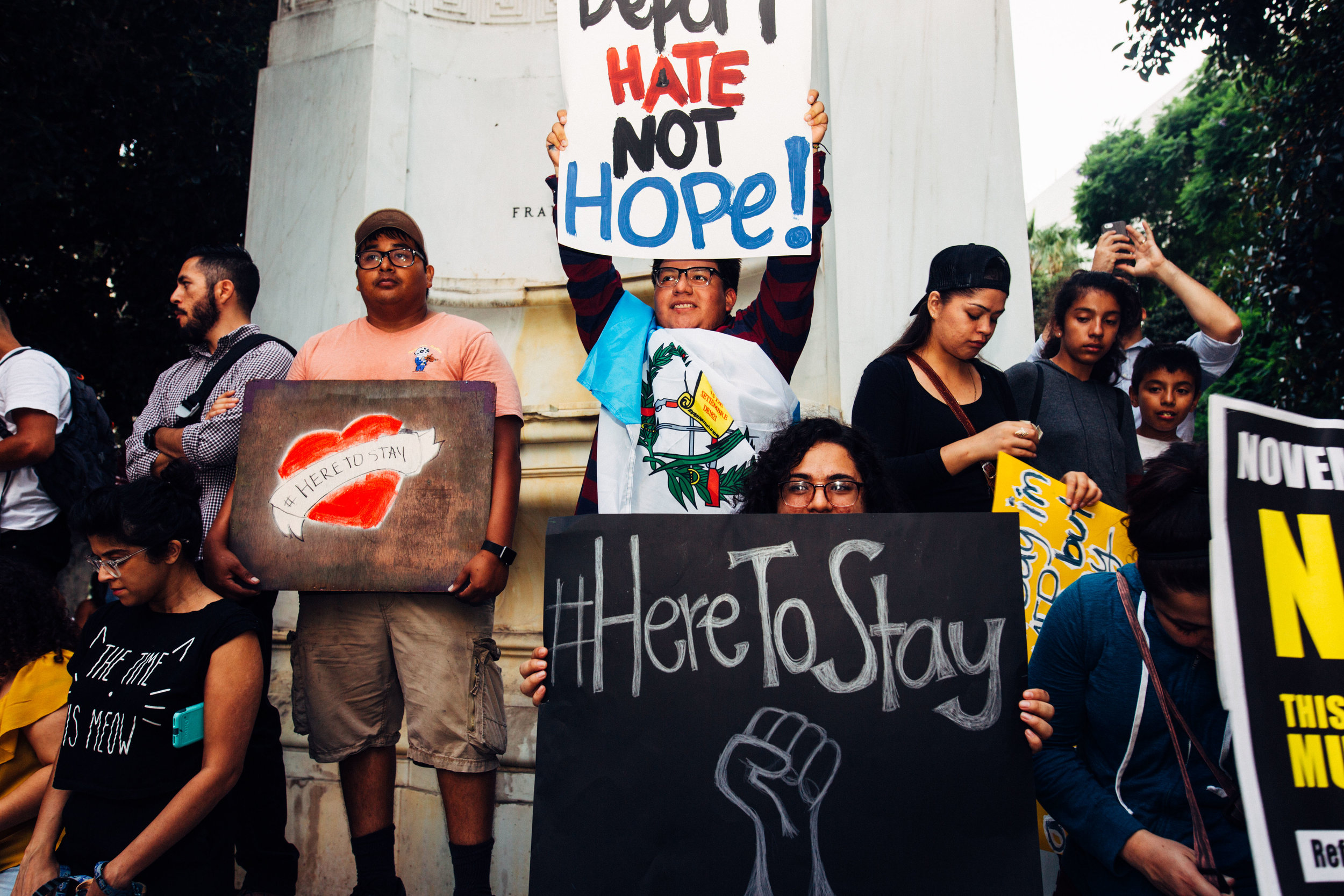 """[Photo description: a group of young protesters stand in front of a marble column holding signs that read """"Here to stay"""" and """"Hate not hope!""""]"""