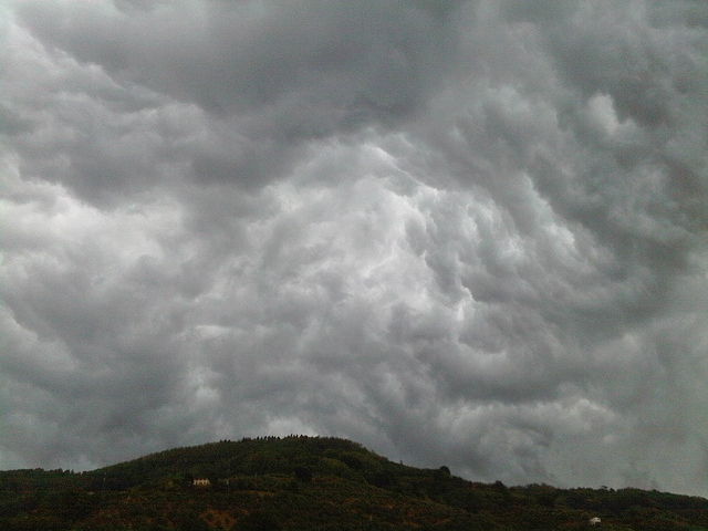 [Image description: photograph of thick, dark clouds above a tree-covered hill.]   Francesco Ugolini / Creative Commons
