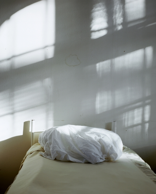 [Image description: photograph of a rumpled pillow lying on a single bed. The pale wall behind the bed is stained by water damage.Window bars cast dark shadows across both the wall and bed.]  Marina Paulenka