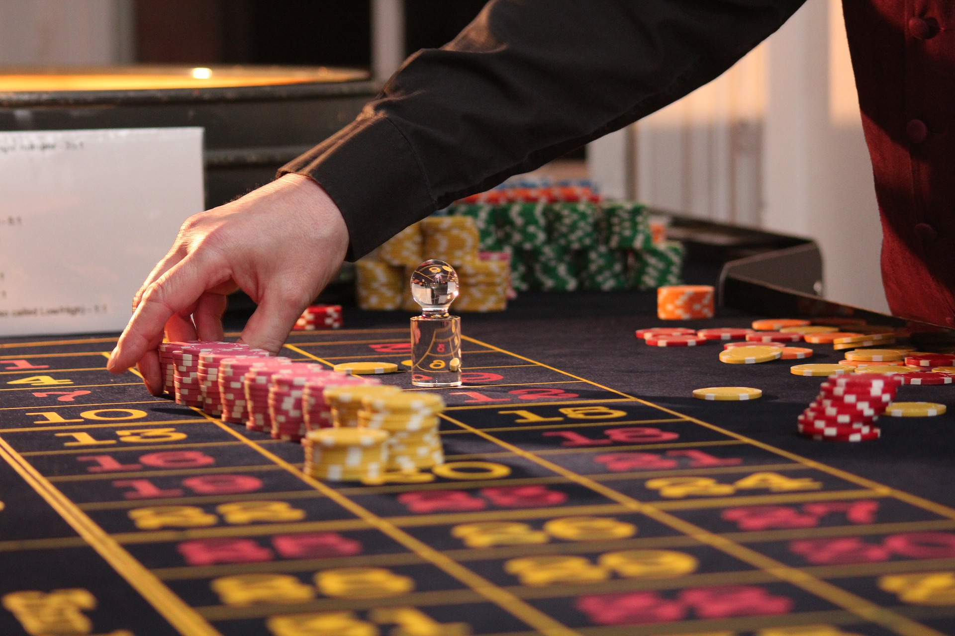 Public Domain. [Photo description: a roulette table piled with stacks of chips, with a dealer's hand reaching across it.]