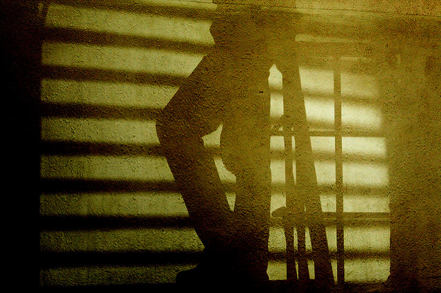 [Image description: photograph of shadows cast by a person standing on an open metal stairwell. Their knee is bent in the centre of the image, facing left, and thick black bars of shadow cut across the image horizontally.]     vinod velayudhan / Creative Commons