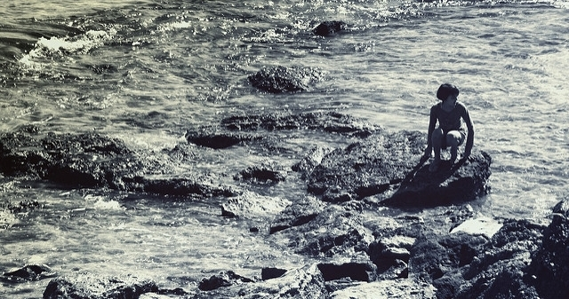 [Image description: black-and-white photograph of a person crouching on a rock in the ocean. Their rock is surrounded by others, flat and pock-marked by water erosion. The current is strong.]  Capture The Uncapturable / Creative Commons