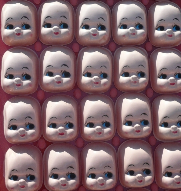[Image description: photograph of rows of dolls' faces. They are identical apart from one or two chips or smudges.]   Dennis Yang / Creative Commons