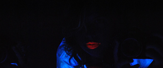 [Image description: photograph of a person sitting beneath a blacklight. All that can be seen of their face is the bright outline of their lipstick.Some pale material around their shoulders shows the silhouette of their face and hair.]   Paulina Spencer / Creative Commons