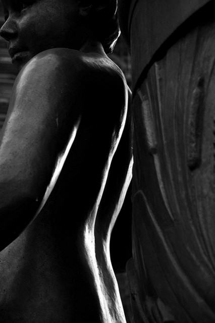 [Image description: black and white photograph of a statue of a young person cast in dark metal. Their back faces the camera and is illuminated from behind, and they are looking over their left shoulder.]   tomvdh1 / Creative Commons