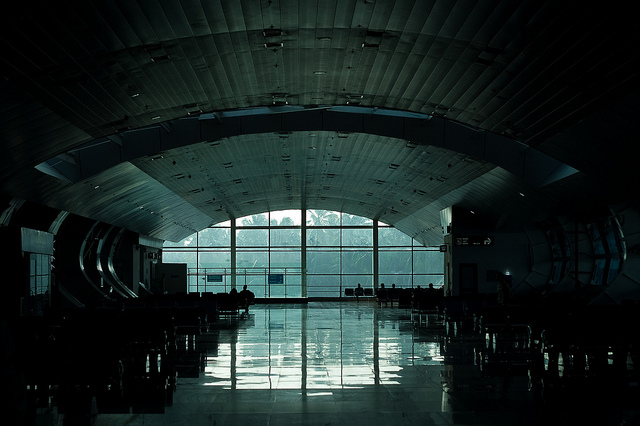 [Image description: photograph of a dimly lit airport terminal. There is a large, bright window in the centre of the image, at the end of a short corridor beneath a slightly arched ceiling. Silhouettes of people sitting in chairs can be seen along the bottom of the window.]   Gerald Pereira  / Creative Commons