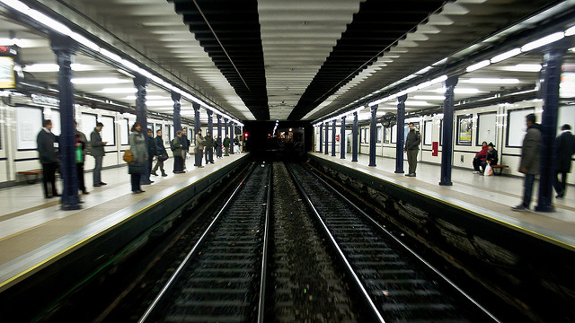 [Image description: photograph of an underground train platform, taken from the tracks and facing into the tunnel. A few people line the platforms on either side of the tracks, and the front of a train is visible in the right side of the tunnel.]   Hernán Piñera  / Creative Commons