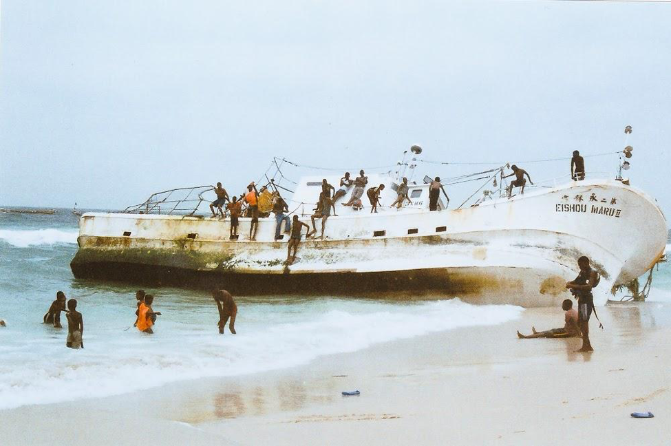 [Image description: photograph of a ship run aground, lying on its side. The tide of pale water is coming in. People are sitting on the raised side of the ship, and standing in the water and on the beach.]  Nanette Thiam