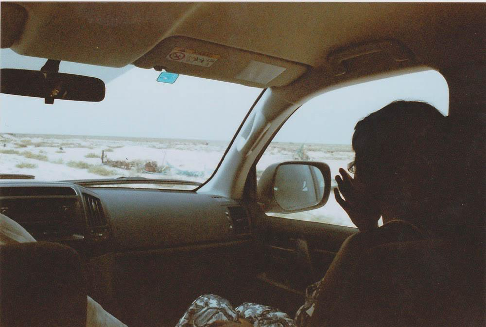 [Image description: photograph taken from the back seat of a moving car. The person sitting in the front passenger seat is visible in profile. Desert scenery and a cloudless sky can be seen through the windshield and front passenger window.]  Nanette Thiam