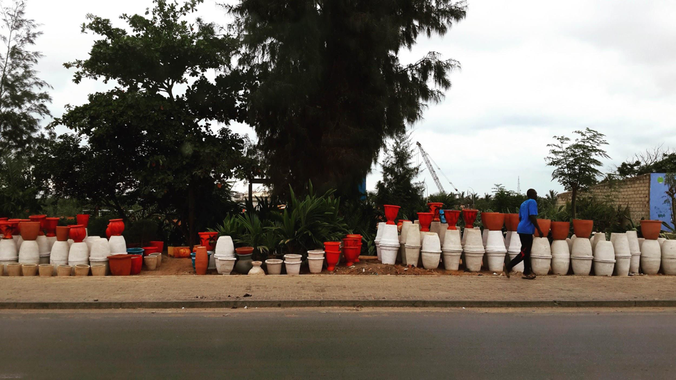 [Image description: photograph of plant pots, of varying size and colour, stacked together along the side of a street. There is a single person passing by, an a large, dark-leafed plant in the centre of the image.]  Nanette Thiam