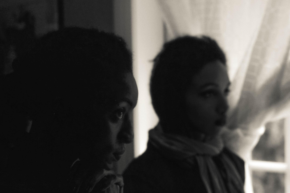 [Image description: black and white photograph of two people in profile, both of whom are wearing scarves around their necks. They are standing inside, by a brightly lit window with a thick white curtain tied to the side.]  Nanette Thiam