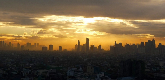 [Image description: photograph of a wide city skyline at sunset. The sun seems to be directly above the highest buildings in the centre, and the light gradually fades from bright at the top to dark at the bottom of the image.]  SteffyWonder / Creative Commons