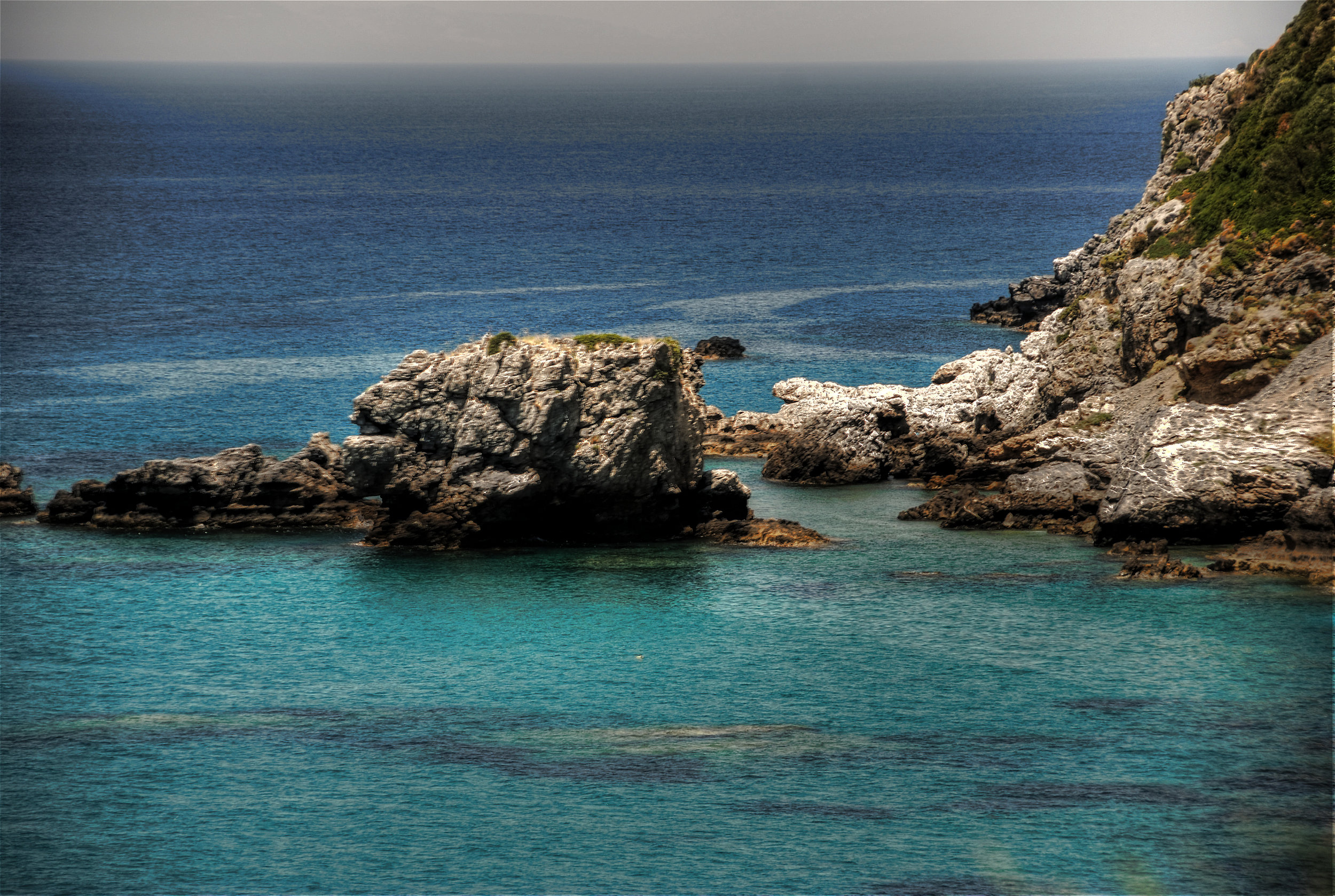 Photo credit: Tony Bevington   [Image description: craggy, rough cliffs rising from a calm Aegean sea]