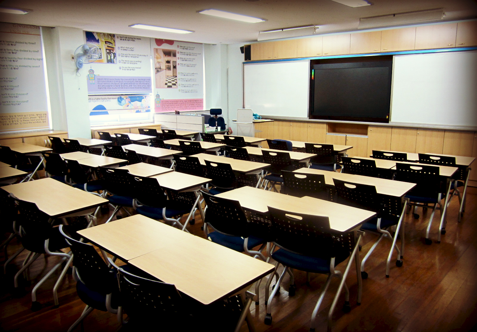Photo: Cali4beach / Creative Commons   [Image description: A classroom with many  desks facing a whiteboard.]