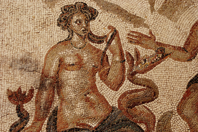 [Image description: photograph of a section of mosaic. It features Galatea, a sea-nymph who resembles a mermaid, naked to the waist with parts of a long scaly tail visible. There is also a small sea monster, and the hand and arm of another person visible at the right side of the image. The ancient tiles have faded in colour to an almost sepia tone.]  Carmen Escobar Carrio / Creative Commons