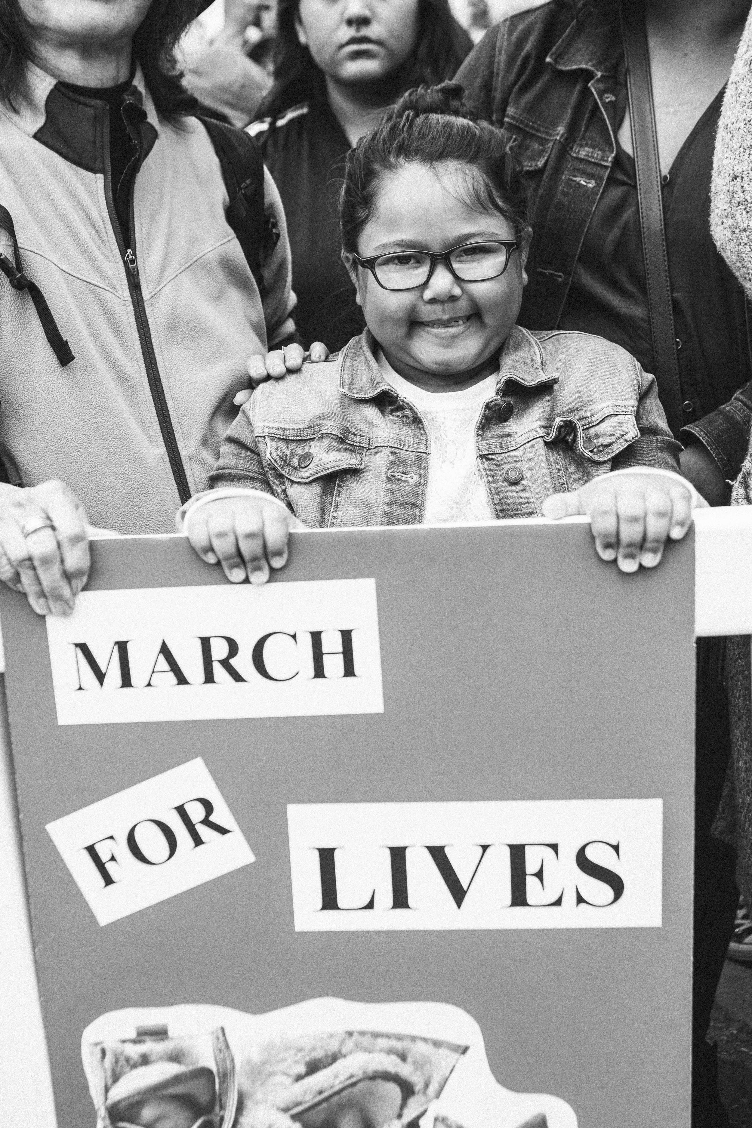 "[Image Description: A photo of Samantha, an eight year old with glasses and cherubic cheeks holding a sign with the world ""March for our lives.""]"