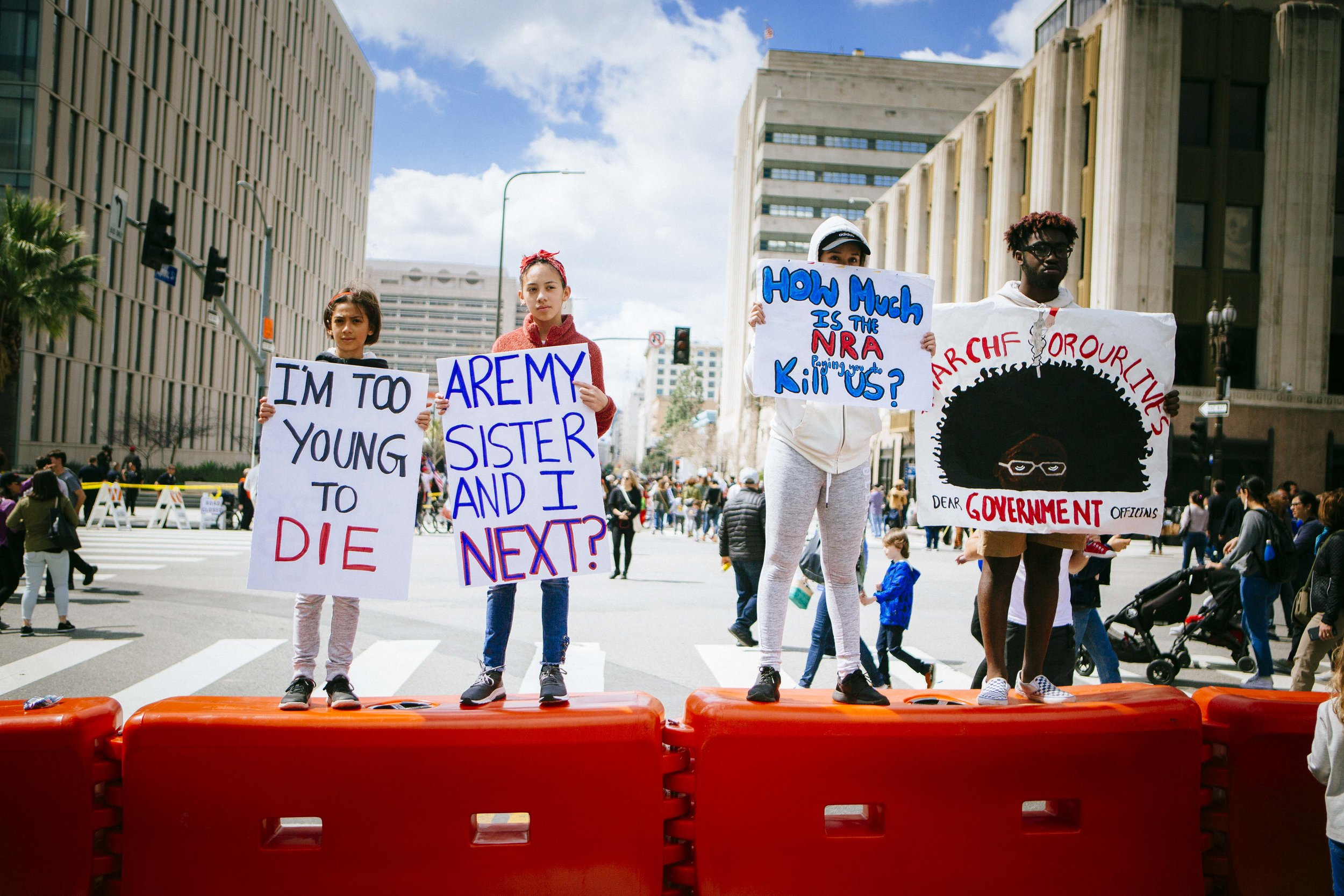 "[Image Description: Four young people stand on a red barrier holding signs. The first sign says ""I'm too young to die."" The second sign says ""Are my sister and I next?"", the next sign says ""How much is the NRA paying you to kill us?"" The last sign has a drawing of the top of a black person's head with a large afro, and around the afro says ""March for our lives"" underneath the eyes says ""Dear Government Officials""]"