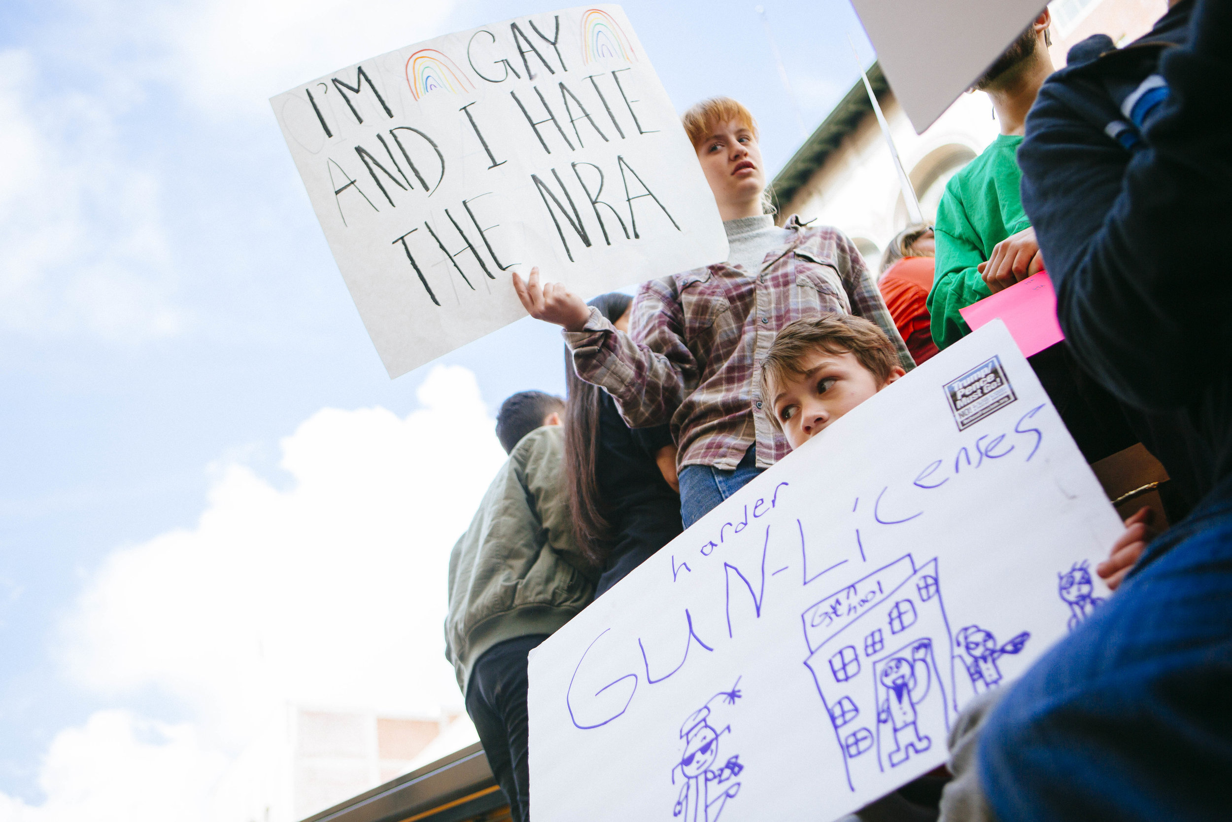 "[Image Description: A person stands against the sky with a sign that says ""I'm gay and I hate the NRA. To their left is a child with a hand written sign advocating for ""harder gun-licenses"" The child's sign has a drawing of a 'gun school' with little figures going in.]"