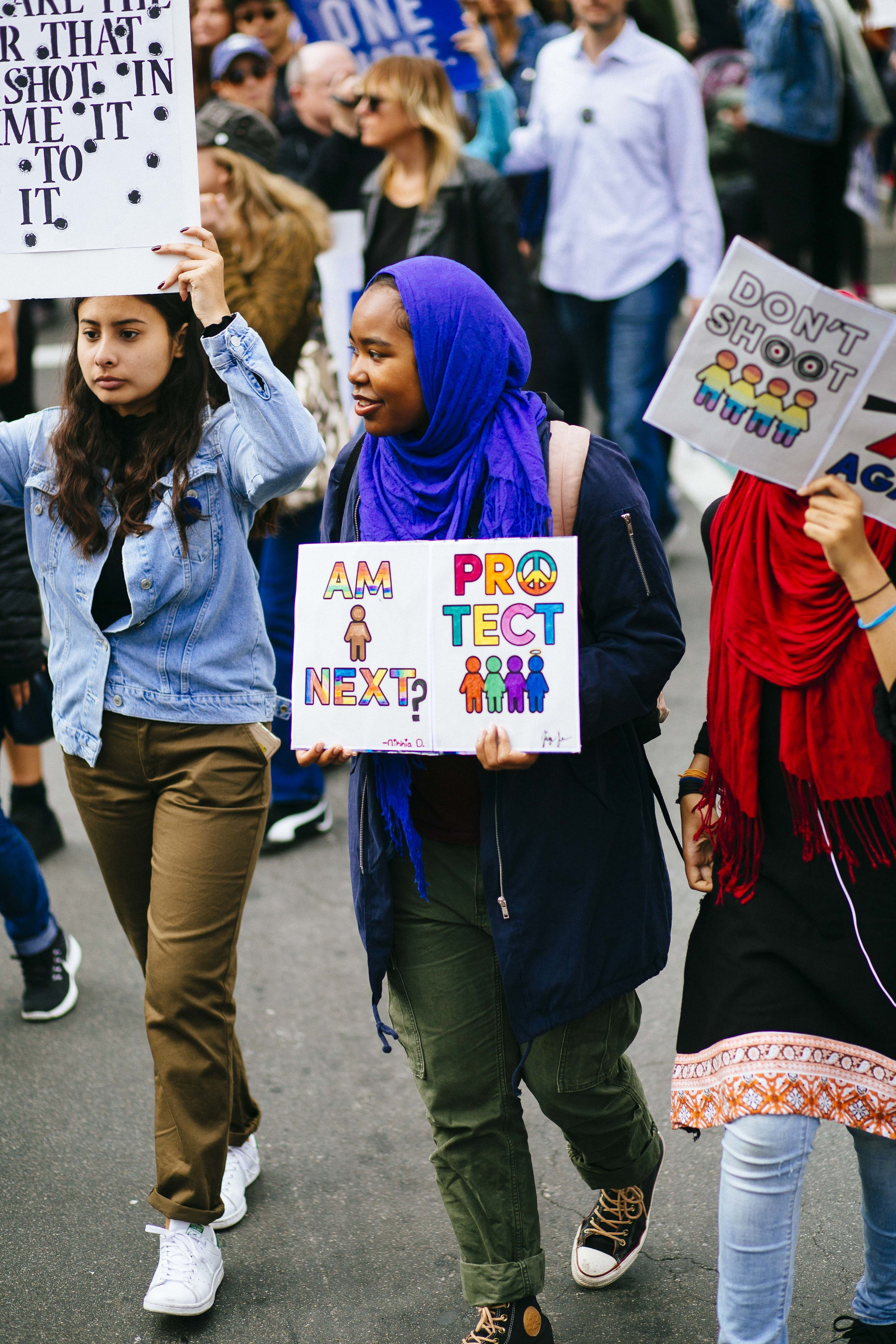 "[Image Description: Three people walk down a street holding signs. The photo is focussed on a woman in a hijab holding a sign with the words ""Am I Next? Protect"" with a drawing of little colourful people]"