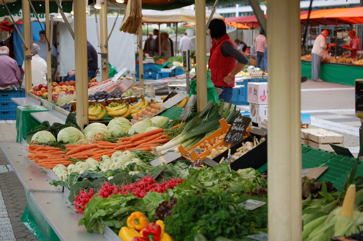 Wikimedia   [Image description: photograph of an outdoor marketplace stall filled with fresh fruits and vegetables of all colours and sizes.]