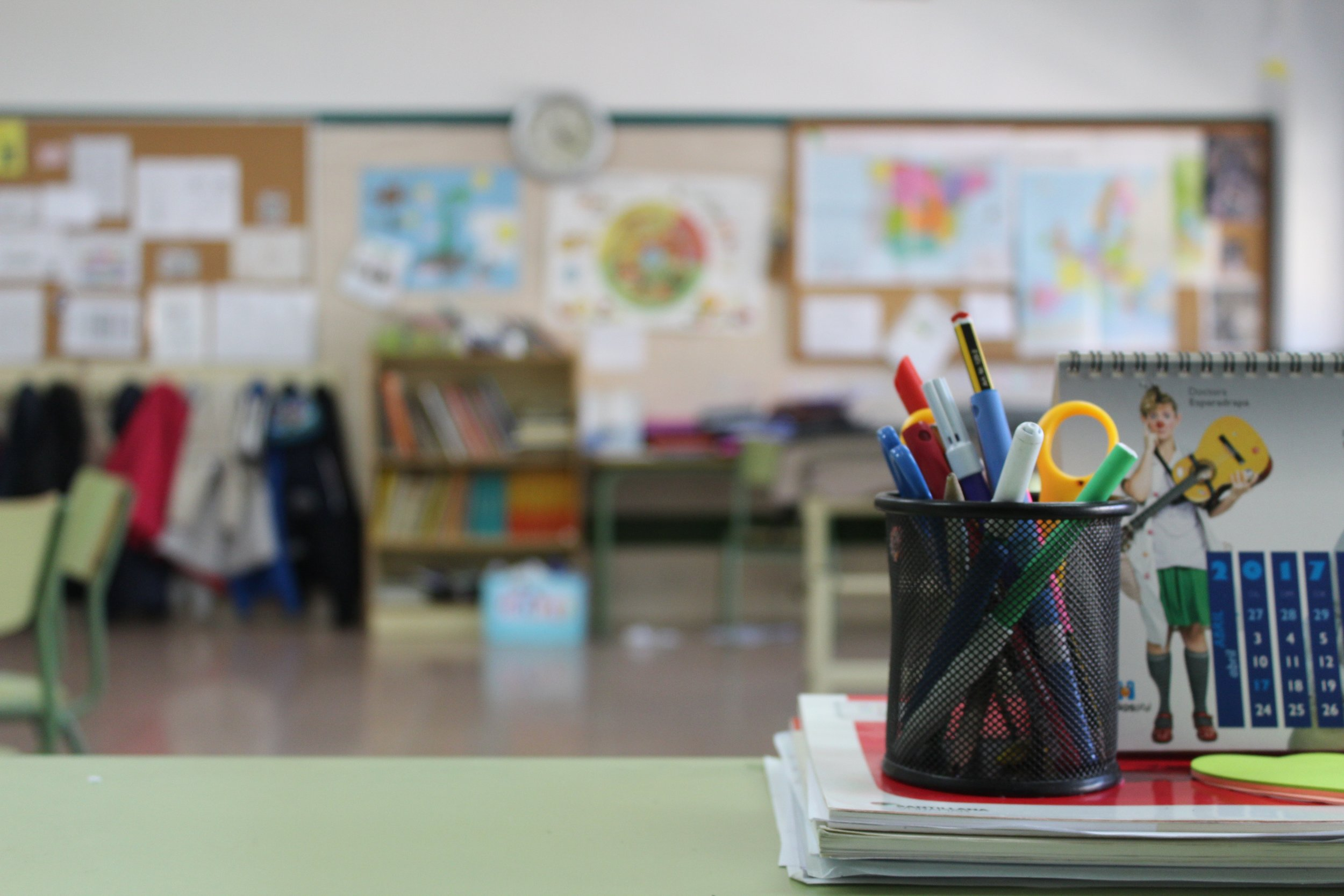 Celia Ortega  /  Unsplash      [Image description: colored photograph of a children's classroom, blurry background filled with coats, pictures, and books. A calendar and a full pencil holder sits in the clear foreground]