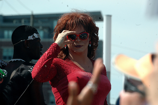 [Image description: photograph of a person with curly auburn hair looking straight at the camera. They are wearing a red dress,red sunglasses, and dark lipstick. To their left is a person wearing a black sash and a diamond tiara.]  Steve Baker / Creative Commons