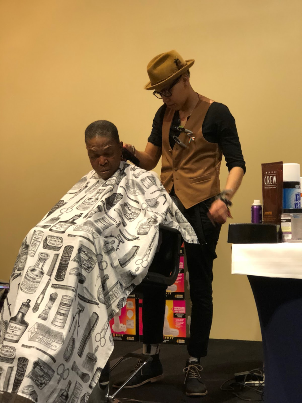 [Image description: photograph of the same two people in a barber shop. The person on the left is seated, facing the camera, and wearing a white barber cape. The person standing behind them is cutting their hair with clippers.]  Photo credit Mr. Cook