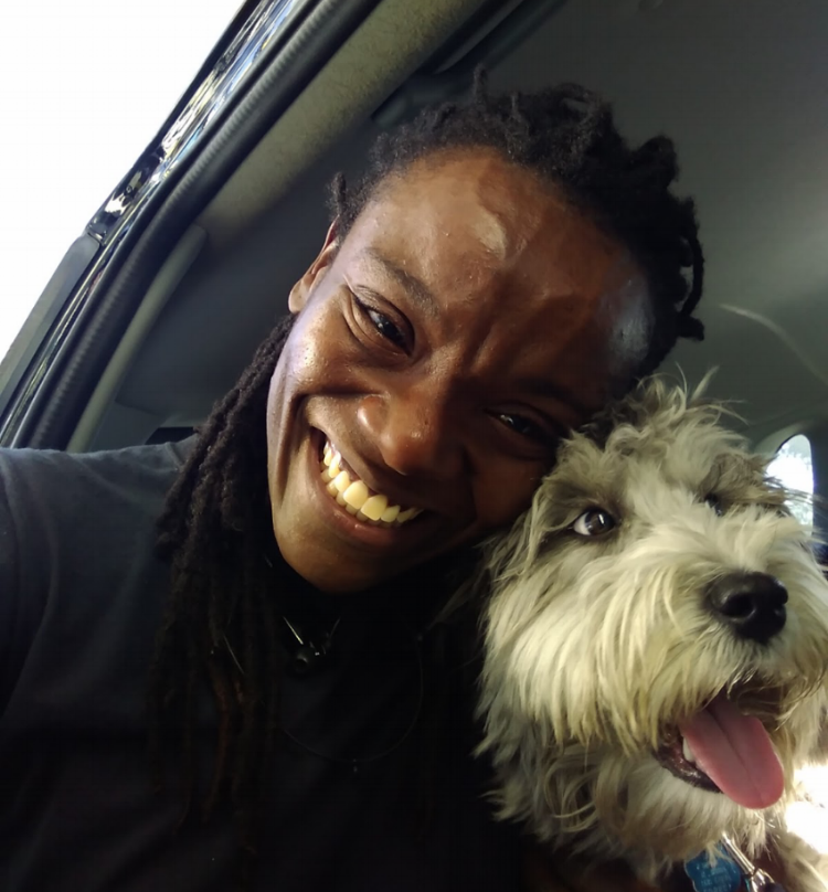[Image description: photograph of a person, taken from below. The person is smiling, and is holding a white shaggy dog on the left side of the image.]  Photo credit Lyn