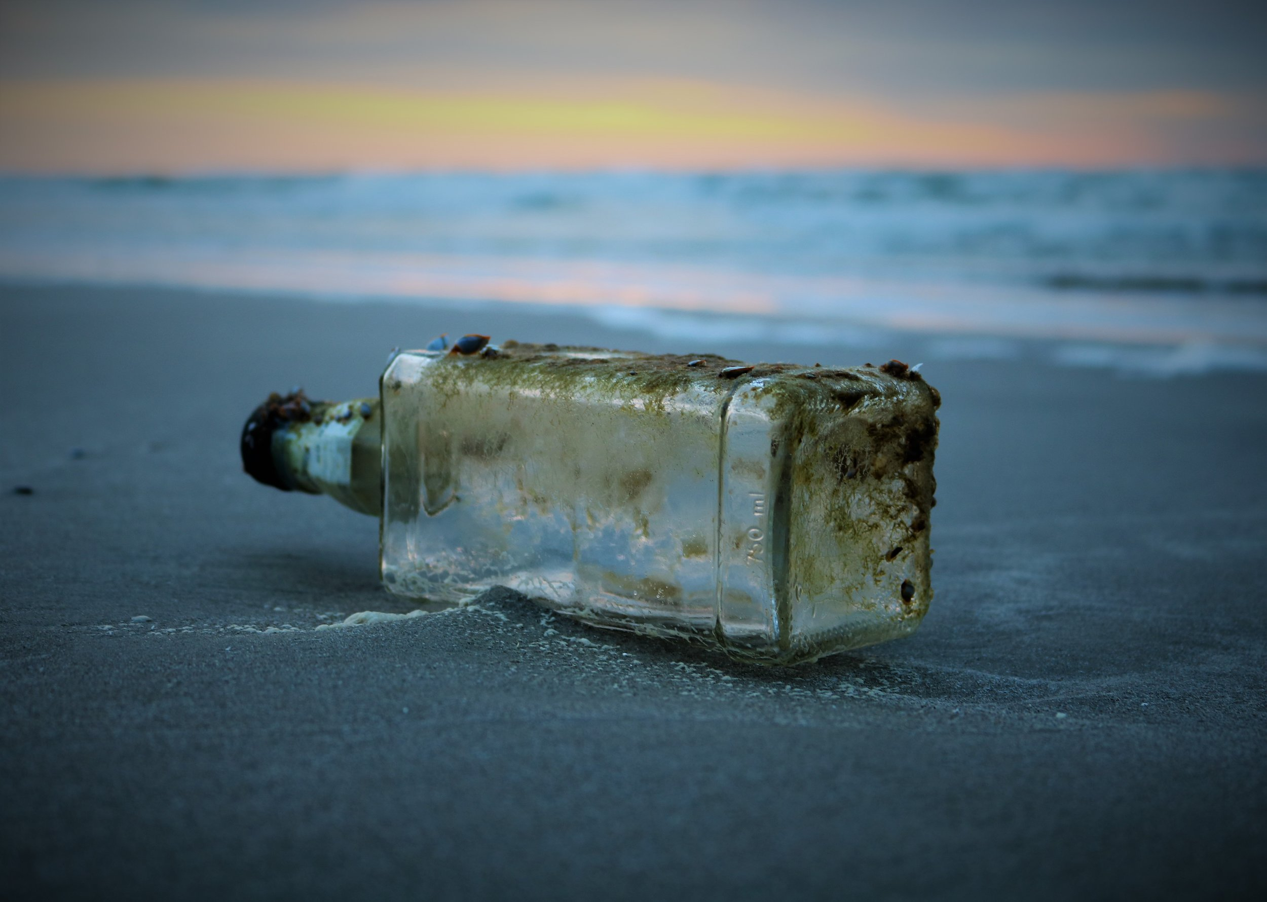Photo by  Scott Van Hoy on  Unsplash    [Image Description: An aged glass bottle, encrusted with sand and grime, washed upon the beach shore.]